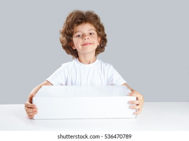 The charming little boy gives a blank white box. He looks into the camera. Gray background. Close-up.