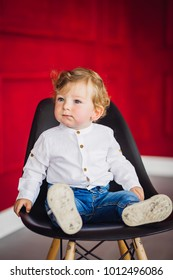 Charming little boy sits on the chair in a cosy red room