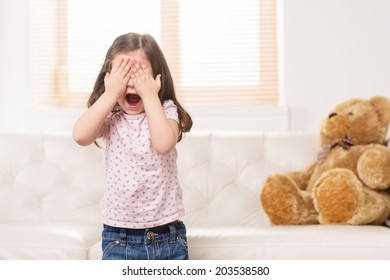 charming little girl covered eyes. nice girl playing hide and seek