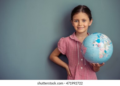 Charming little girl in cute dress is holding a globe, looking at camera and smiling, standing on gray background