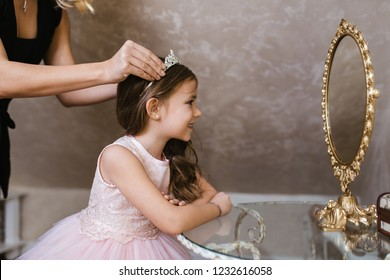 Charming little girl dressed in beautiful fashion dress with her mother preparing for important event.