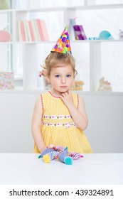 charming little girl in a festive hat. child in yellow dress smiling