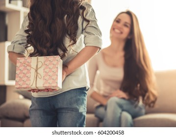 Charming little girl is giving her beautiful young mom a present, woman is smiling while sitting on couch at home