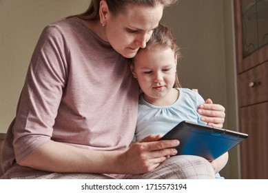 A charming little girl and her beautiful young mother use a digital tablet and smile while sitting on chairs at home. Home schooling and Skype communication, reading books and training materials.