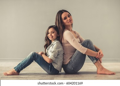 Charming little girl and her beautiful young mom are looking at camera and smiling while sitting back to back on the floor