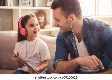Charming little girl and her handsome young dad in headphones are listening to music, using gadgets and smiling while sitting on sofa at home