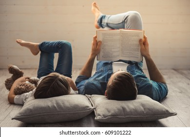 Charming little girl and her handsome young dad are reading a book while lying on the floor at home