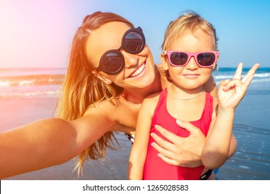 charming little girl and her mom are photographed on the phone