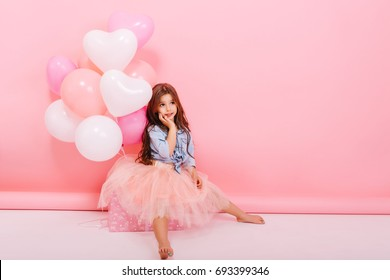 Charming little girl with long brunette hair, in tulle skirt dreaming isolated on pink background. Happy childhood with colorful balloons, birthday party with presents of cute kid