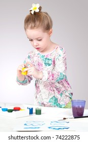Charming little girl mixing colors