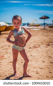 Charming little girl on the beach posing during the summer holid