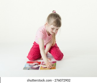 Charming little girl playing on the floor, white background
