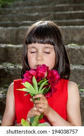 Charming little girl in a red dress sitting on stairs with peony closed eyes