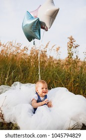 Charming little girl sits with colorful baloons on the white blanket