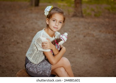 Charming little girl sits near tree in forest with doll in hands
