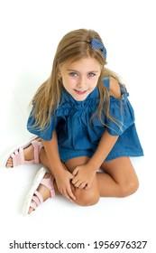 Charming little girl sitting on floor. Studio portrait.