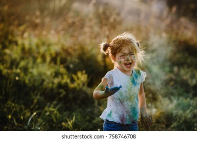 Charming little girl with white shirt covered with different paints
