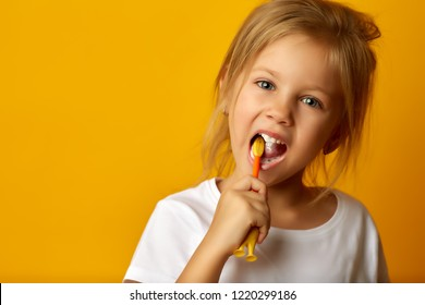 Charming little girl in white t-shirt cleaning teeth with colorful kids toothbrush looking at camera