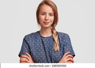 Charming lovely young female with appeallig appearance, has plait, wears polka dot blouse, going to have meeting in cafe with former classmates, looks confidently at camera, being in good mood