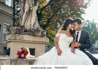 Charming loving just married couple is hugging and sitting on the fountains near the wedding bouquet of red flowers.