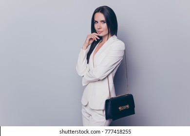 Charming magnificent attractive woman with straight dark hair dressed in white suit with a black clutch bag is standing against grey background, copy space