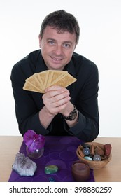 Charming male gypsy fortune teller with tarot cards