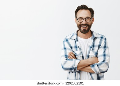 Charming male professor of university standing over gray background in stylish sunglasses and checked shirt, talking casually with colleagues about job and funny moments during tutoring, smiling