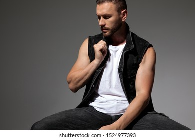 Charming man adjusting his jeans vests collar and looking to the side while sitting with his legs apart on gray studio background