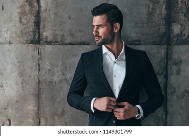 Charming man. Handsome young man in suit looking away and adjusting his jacket while standing indoors