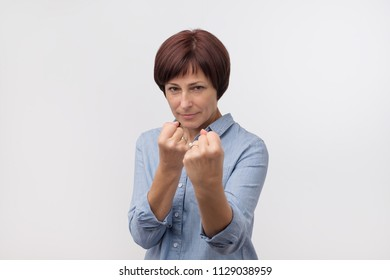 Charming mature caucasian woman in blue shirt raising fists, standing in boxer pose. She is ready to fight with problems and enemies