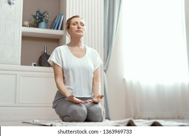 Charming Mature Woman Meditates Seating On Her Knees. Practicing Yoga Concept. Mindfulness