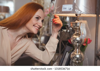 Charming mature woman smiling joyfully, choosing new lamp at home furnishings store. Happy female customer buying home goods at homeware store. Housewife shopping concept