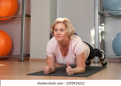 Charming Middle aged woman standing in plank position after a workout. The concept of health and longevity