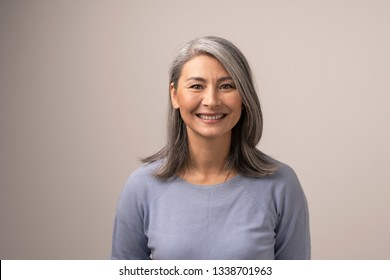 Charming Middle-Aged Asian Woman Broadly Smiles At Camera. Horizontal Studio Shot Of Graceful Smiling Woman. Portrait