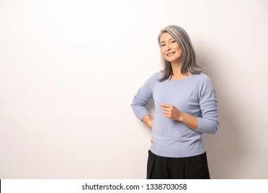 Charming Middle-Aged Asian Woman In Casual Cloth Smiling At Camera. Attractive Grey-Haired Woman Standing In Front Of White Wall And Posing. Waist-Size Portrait.