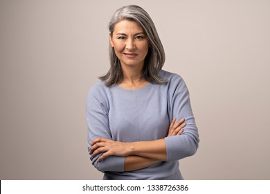 Charming Middle-Aged Woman With Crossed Arms Twists Her Face In Disgust. Asian Woman Shows Her Disapproval By Twisting Her Lips And Crossing Arms. Portrait.