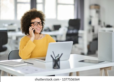 Charming mixed race businesswoman dressed casual using smart phone and laptop at the same time while sitting in modern office.