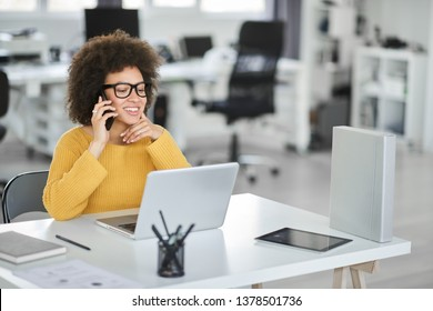 Charming mixed race businesswoman dressed casual using smart phone while sitting in modern office.