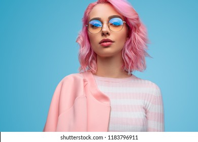 Charming modern hipster woman with pink short hair wearing pink jacket and glasses looking sensually at camera on blue background