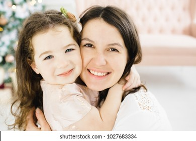Charming mom and her pretty little daughter pose before a rich Christmas tree in a luxury white room