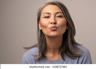 Charming Mongolian Woman with Gray Hair Over a Gray Background. She Gently Sends a Kiss to the Frame. Mongolian Beauty Concept. Close Up Shoot.