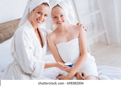 Charming mother and daughter being satisfied of nourishing cream