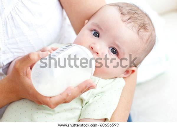 Affascinante madre alimentazione il suo adorabile figlio in il cucina a casa