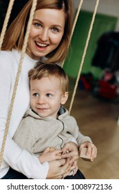 Charming mother has fun with her son playing on the swing in cosy room