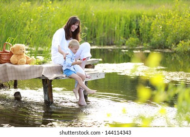Charming mother with a young son playing at the lake in the Ukrainian countryside