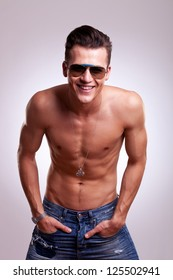 charming muscular topless young man holding his hands in his pockets and smiling at the camera