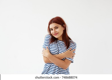Charming mysterious young female dressed in striped t-shirt embracing herself, looking at camera and smiling broadly, feeling shy or cold. People, lifestyle, youth, joy and happiness concept