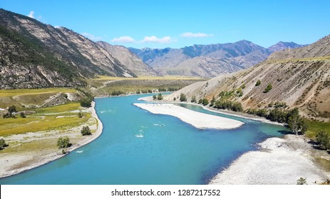 The charming nature of mountains, seas and rivers, green grass. Altai. Against the blue sky, sandy beach.
