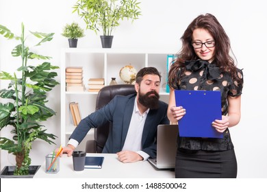 Charming nerd. Sexy female employee with nerd look standing in front of employer. Adorable nerd girl and businessman working in office. Sensual secretary wearing nerd glasses and bearded boss at work.
