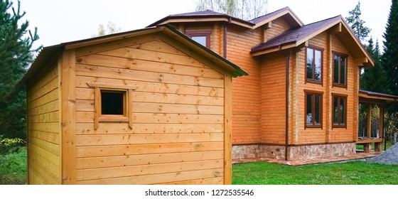 Charming new  home exterior, natural wood and brown siding. Wall of modern building wooden planks and green grass
